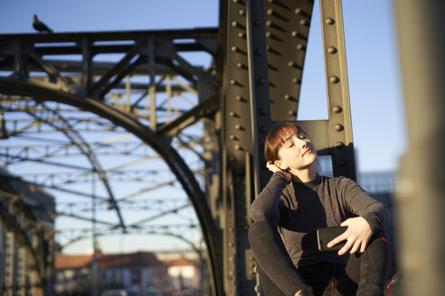 Portrait of relaxed young woman sitting on steel girder of a bridge listening music with smartphone - PNEF01565