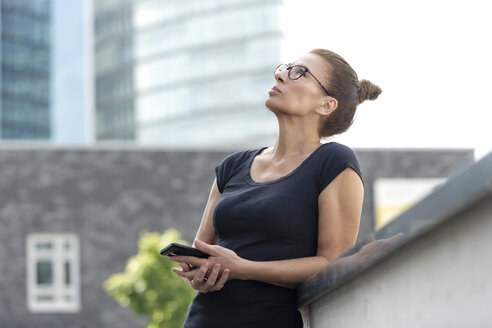 Woman with cell phone in front of office building looking up - FLLF00227