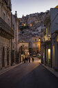 View from an alley in Ragusa Ibla to Ragusa Superiore at dusk, Ragusa, Sicily, Italy - MAMF00764