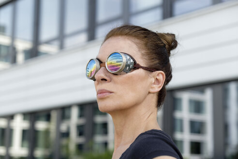 Mature woman wearing welder's goggles in front of an office building - FLLF00232