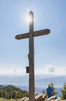 Hiker resting at summit cross, Lammersdorf Mountain, Nock Mountains, Carinthia, Austria - GWF06084