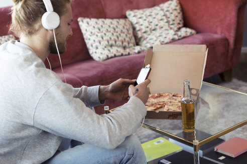 Young man on couch with cell phone and headphones eating pizza - JSRF00181