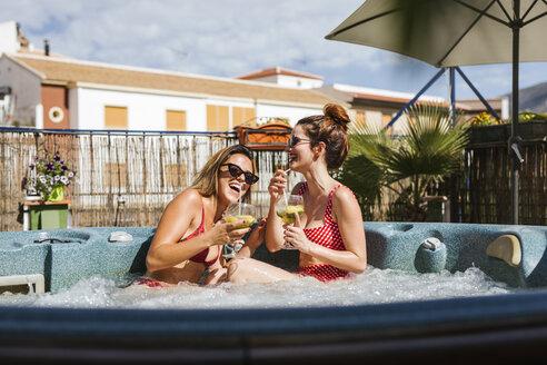 Two happy women having a drink in a jacuzzi - LJF00133