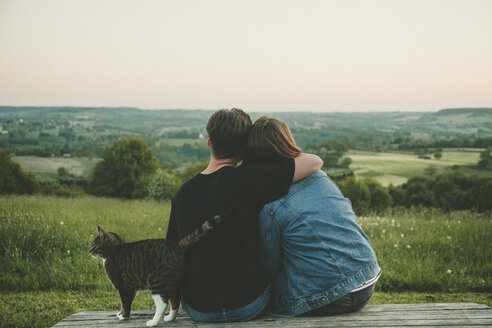 Back view of young lovers with cat enjoying nature at sunset - ANHF00118