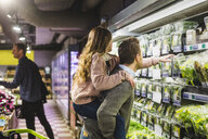 Side view of daughter picking up vegetable packet while being piggybacked by father in store - MASF12430