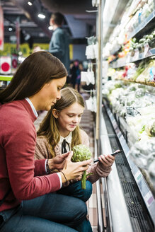 Mother holding artichoke while daughter using mobile phone in supermarket - MASF12433