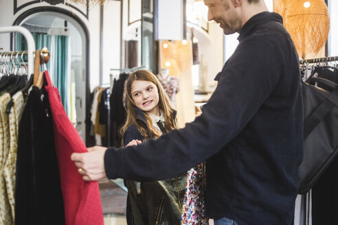 Father showing clothes to daughter in boutique - MASF12466