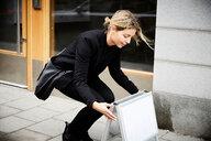 Real estate agent arranging blank signboard on sidewalk in city - MASF12475