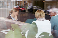 Female realtor discussing with senior couple in office - MASF12499