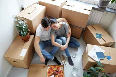 High angle view of couple resting together while having pizza during relocation of new house - MASF12505