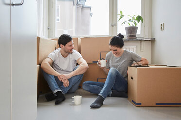 Smiling couple talking while enjoying coffee during moving house - MASF12508