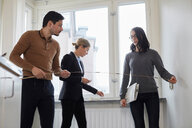 Couple taking measurements while standing with realtor in new house - MASF12517
