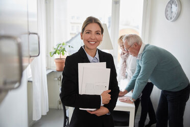 Portrait of smiling real estate agent holding documents with senior couple in background - MASF12520