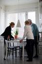 Full length of estate agent explaining documents of new house to senior couple - MASF12523