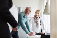 Smiling senior couple looking at real estate agent while signing for new house - MASF12538