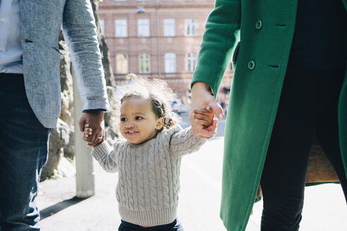 Happy girl walking with midsection of parents in city - MASF12550