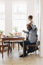 Father carrying daughter on shoulder while using laptop at table in house - MASF12559