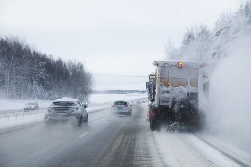 Snowplow and cars moving on snow covered highway - MASF12604