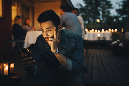 Man using mobile phone while friends in background during dinner party - MASF12613