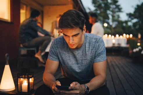Young man using smart phone while friends in background during dinner party - MASF12616