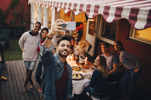 Smiling young man taking selfie with friends during dinner party - MASF12631