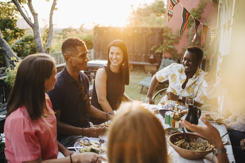 Happy friends talking while enjoying food in dinner party - MASF12658