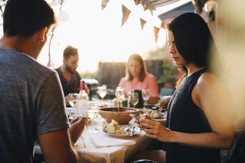Woman using smart phone while sitting with friends at dining table in dinner party - MASF12664
