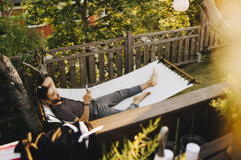 High angle view of young man using mobile phone while lying in hammock at yard - MASF12670