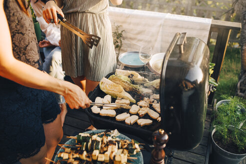 Midsection of female friends grilling food on barbecue grill at yard - MASF12676