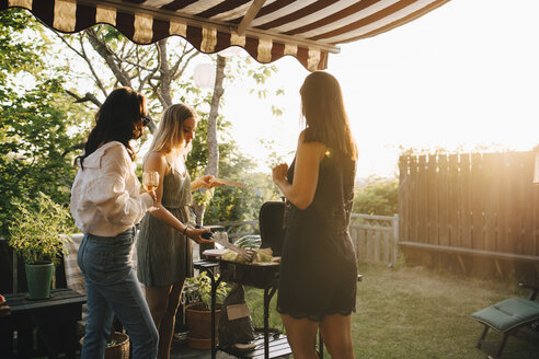 Female friends talking while preparing food on barbecue grill in dinner party - MASF12679