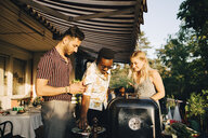 Friends talking while enjoying grilled food at dinner party in back yard - MASF12682