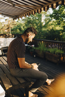Full length of man using smart phone while sitting on bench at back yard - MASF12694