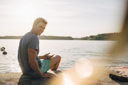 Portrait of smiling young man sitting with mobile phone on jetty by lake - MASF12700