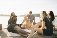 Multi-ethnic friends enjoying food and drink while sitting on jetty at lake against sky - MASF12709