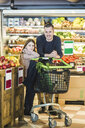 Full length portrait of father and daughter grocery shopping in supermarket - MASF12754
