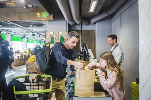 Father and daughter packing groceries in paper bag at checkout counter - MASF12763