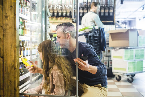 Side view of father and daughter choosing drinks in refrigerator at grocery store - MASF12766