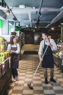 Smiling salesman sweeping floor while looking at colleague in supermarket - MASF12778