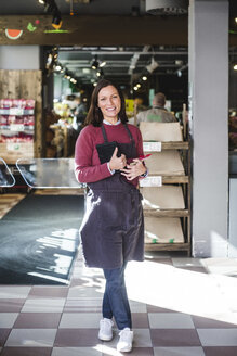Full length portrait of smiling mature saleswoman wearing apron while standing in store - MASF12781
