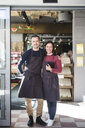 Full length portrait of confident smiling owners wearing aprons while standing in store - MASF12784