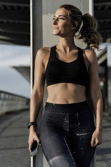 Sporty woman with headphones standing on bridge, listening music, using smartphone - ERRF01464