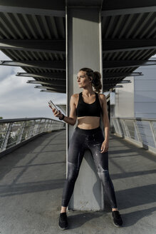 Sporty woman with headphones standing on bridge, listening music, using smartphone - ERRF01467