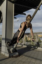Sporty woman working out o a bridge, leaning on bar - ERRF01476