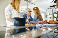Mother, daughter and grandmother having fun, chopping strawberries in the kitchen - ZEDF02334