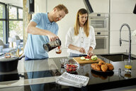Couple standing in kitchen, preparing healthy breakfast, chopping fruits - ZEDF02349