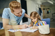 Father and daughter sitting at table, painting colouring book - ZEDF02358