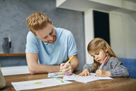Father and daughter sitting at table, painting colouring book - ZEDF02361