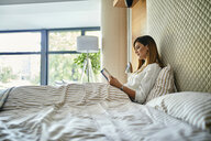 Woman sitting in bed, reading a book - ZEDF02394