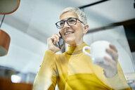 Senior woman drinking coffee, talking on the phone - ZEDF02403