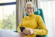Senior woman with headphones using smartphone - ZEDF02409